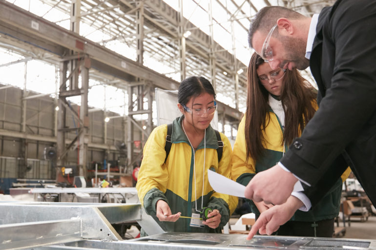 two female school children with an adult male completing a STEM activity